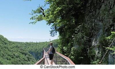 Young woman walks on observation deck. Okatse Canyon, near Kutaisi, Georgia