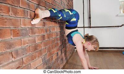 Young woman warming up in a studio. Leg stretching near by wall