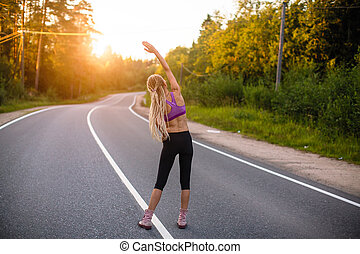 Young woman warms-up before jogging on the country road.