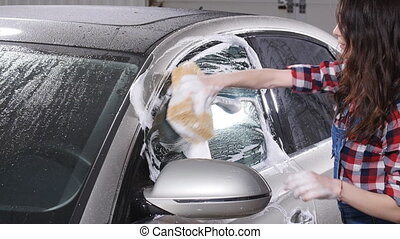 Young woman washes the car with a sponge