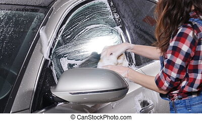 Young woman washes the car with a sponge - young woman...