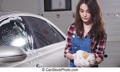 Young woman washing a car with a sponge - Young Woman...