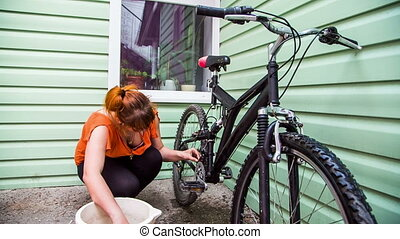 Young Woman Washing Bicycle Wheels - This is a process of...