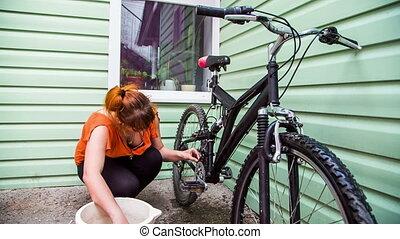 Young Woman Washing Bicycle Wheels
