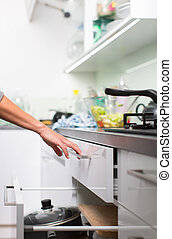 Young woman washing dishes in her modern kitchen