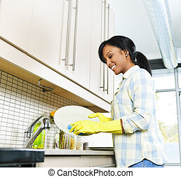Young woman washing dishes - Smiling young black woman ...