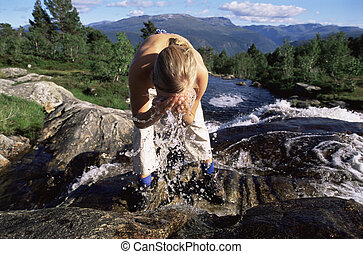 Young woman washing face in river