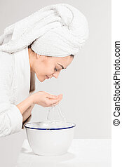 Young woman washing face with clean water