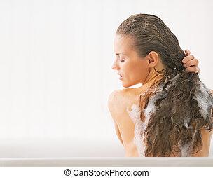 Young woman washing hair in bathtub