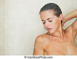 Young woman washing in shower