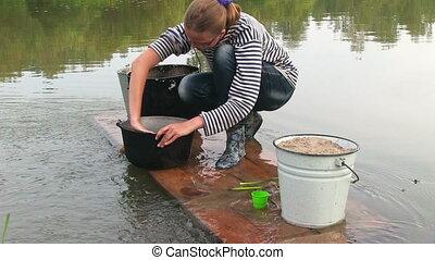 Young woman washing pan