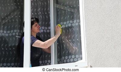young woman washing the window