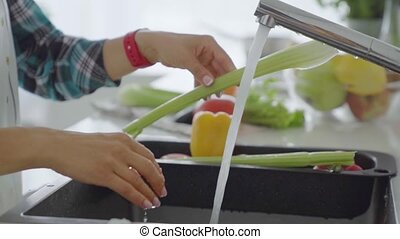 Young woman washing vegetables