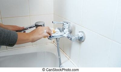 Young woman washing water tap in bathroom with cleanser and...
