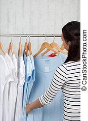 young woman watching shirts in a shop