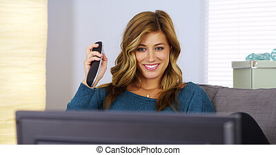 Young woman watching television with remote in hand