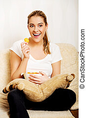 Young woman watching TV and eating chips