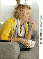 young woman watching tv and eating popcorn on the couch