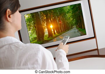 young woman watching tv at home
