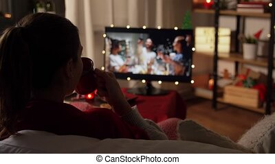 christmas, winter holidays and leisure concept - young woman watching movie on tv and drinking coffee or hot chocolate at cozy home