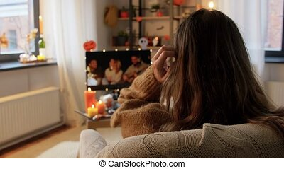 halloween, holidays and leisure concept - young woman watching tv and resting her feet on table at cozy home