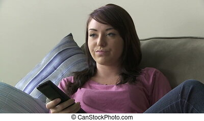 Young woman watching TV - Bored young woman flipping...