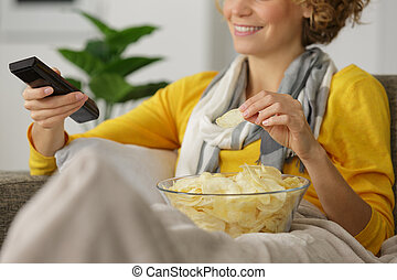 young woman watching tv on the couch at home