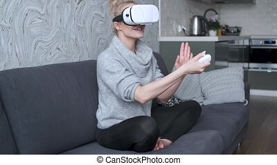 Young woman watching videos or playing with VR glasses on...