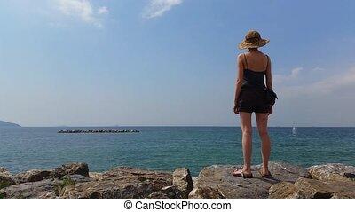 Young Woman watching windsurfers on rocks