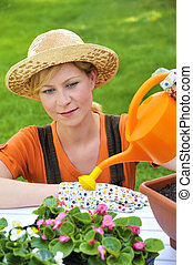 Young woman watering flowers