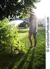 Young woman watering garden - twenty something woman...