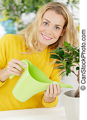 young woman watering indoor flowers