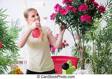 Young woman watering plants in her garden