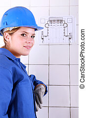 young woman wearing a blue jumpsuite in front of an electrical schema