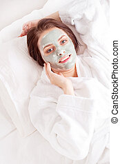 clay mask - young woman wearing a deep cleansing green clay ...