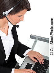 Young woman wearing a headset typing at a keyboard