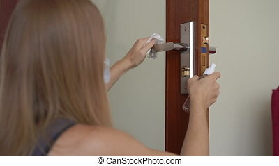 Young woman disinfects door handle during self-isolation. Social distancing concept.