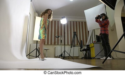 Young woman wearing a sparkly dress being photographed by her husband in an improvised white background studio