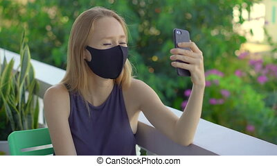 Young woman, wearing a tissue face mask, talks on a smartphone. Fashionable face masks. Social distancing concept