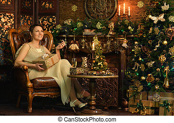 Young woman wearing beautiful golden dress sitting in vintage armchair