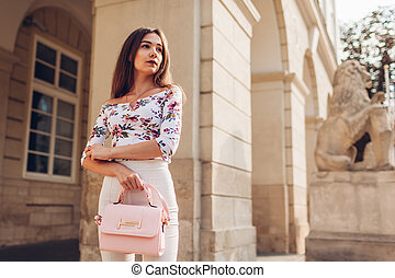 6812330c Young woman wearing beautiful outfit and accessories and shoes outdoors.  Girl holding stylish handbag.