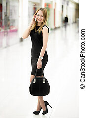 Young woman wearing black clothes on phone