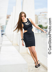 Young woman, wearing black dress, with long hair