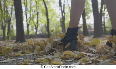 Young woman wearing black shoes with heels stepping on autumn leaves in park on a sunny day in slow motion