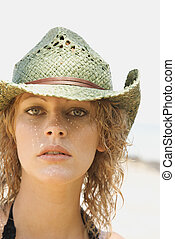 Young woman wearing cowboy hat.