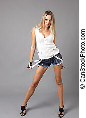 Young woman wearing denim shorts with suspenders.