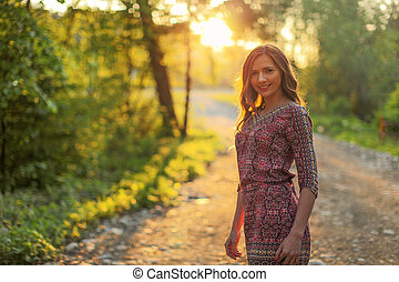 Young woman wearing dress, walking on forest path with golden sunset light in background.