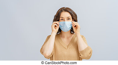 woman wearing facemask - Young woman wearing facemask during...