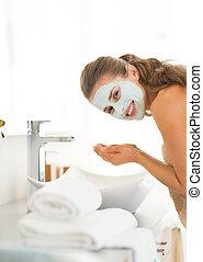 Young woman wearing facial cosmetic mask washing face