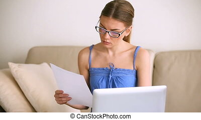 Young woman wearing glasses working with laptop and documents indoors